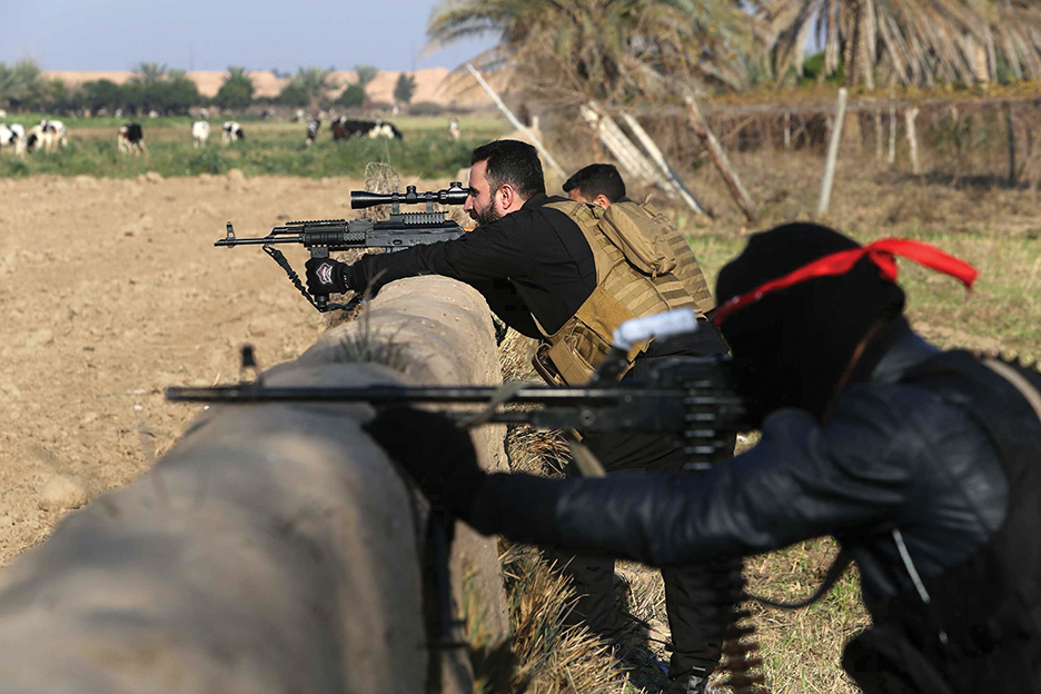 Pro-Iraqi government fighters, some belonging to the Iraqi Imam Ali Brigade, take part in an operation to secure an area they seized from the Islamic State (IS) militants in Yathreb near Balad, about 75 kilometres (45 miles) north of Baghdad on December 29, 2014. Iraqi forces backed by Sunni tribes advanced on December 28 into the town of Dhuluiyah, strategically located on roads linking the eastern province of Diyala to Salaheddin province, north of Baghdad in a new attempt to push out Islamic State group jihadists, officials said.   AFP PHOTO / MOHAMMED SAWAF        (Photo credit should read MOHAMMED SAWAF/AFP/Getty Images)