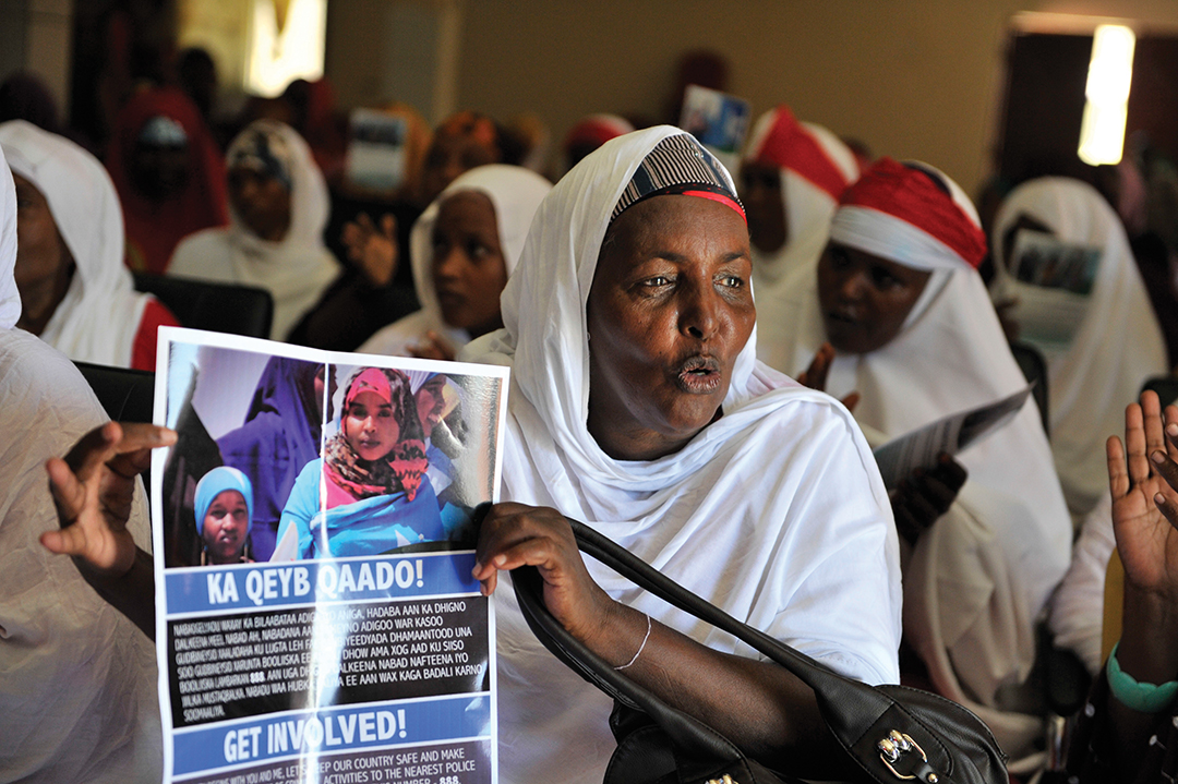 A resident holds a poster encouraging civilian involvement during a community policing meeting in Mogadishu. Somali police have recruited neighborhood volunteers to report suspicious behavior.